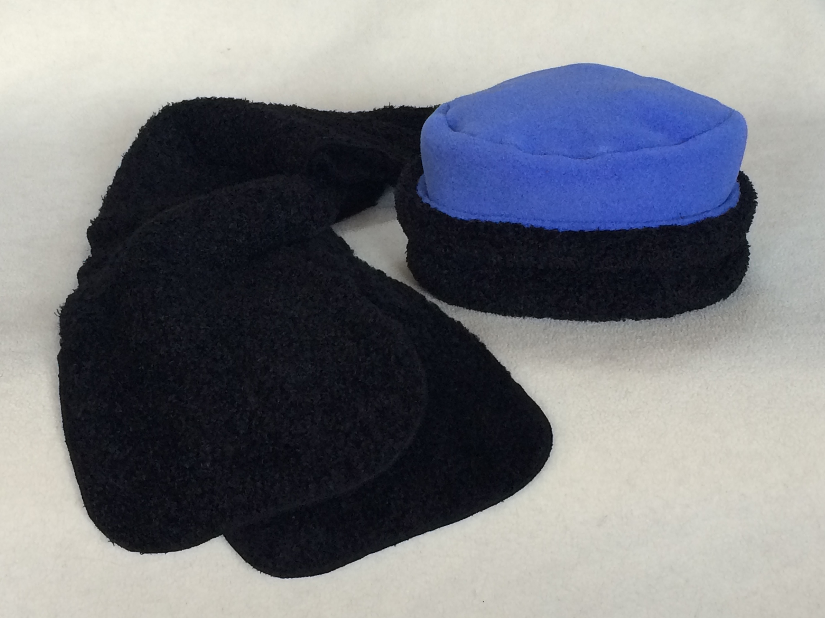 Keep warm with our most popular hat in Periwinkle solid fleece combined with fabulous curly fabric. Double layers of fleece with the super soft curly close to your ears. Paired with a Black Curly scarf and you'll be warm and fashionable. Fabric from Malden Mills, one size fits most.